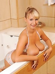 Busty blonde babe Jannete soloing in bathroom rubbing tits